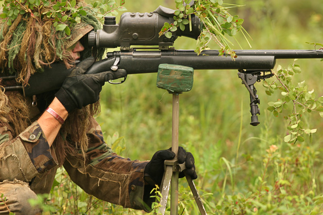 Army sniper uses a lightweight camera tripod to steady his M24 rifle during an exercise.