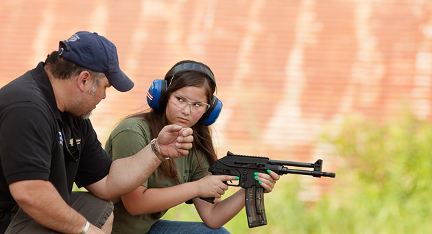 A young shooter with a PLR22 listens to her father's explanation of the course of fire.