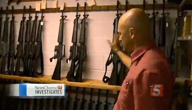 Sheriff Joe Guy and some of the controversial stockpile of military rifles.