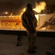 A US Army veteran stands guard on the roof of a shop in Ferguson.