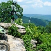 An ATV rider on a rock looking out over a scenic overview. Photo courtesy of the NOHVCC.