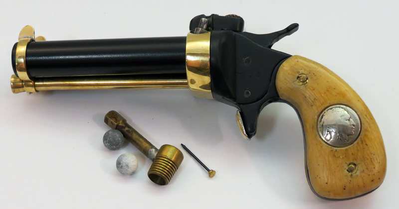 Accessories with the Model MC include a couple old round balls, a powder measure, and the little tool for releasing the ramrod. Photo © Russ Chastain