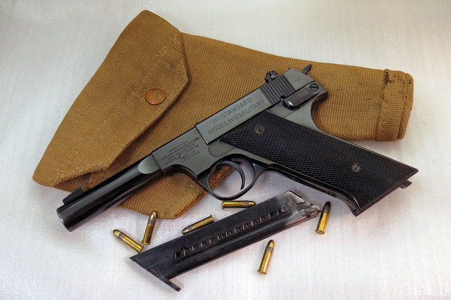 High Standard H-D Military pistol with old GI holster, spare magazine, and ammo. (Photo © Russ Chastain)