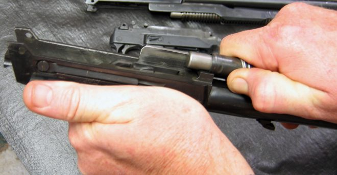 Removing Ruger Carbine action spring, slide, and magazine tube assembly. (photo © Russ Chastain)
