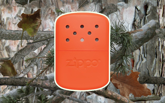 Zippo 12-hour hand warmer in blaze orange on realistic 3D forest camo background