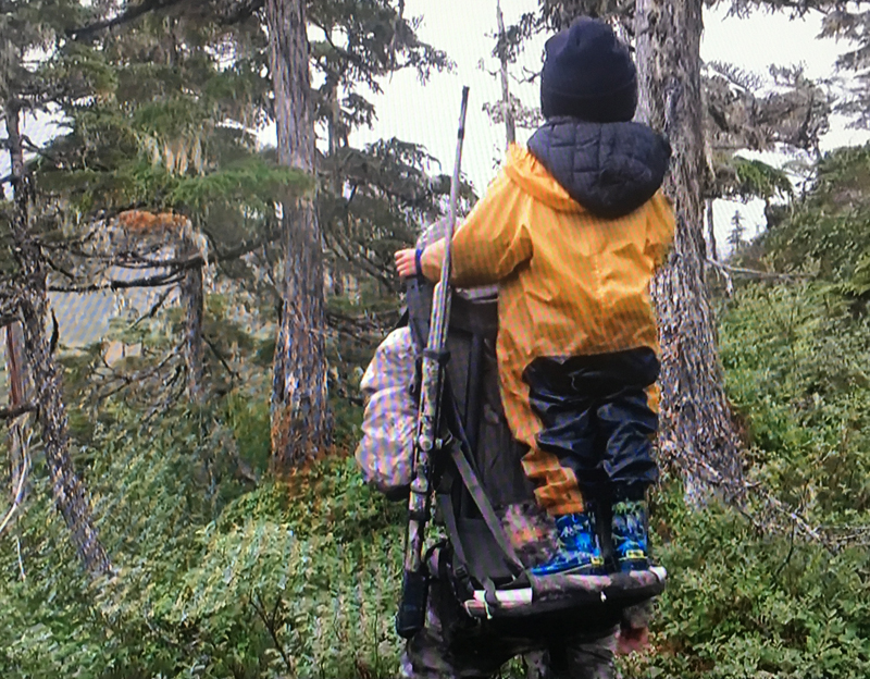 Eivin Kilcher carries his son Findlay on a backpack while hunting.