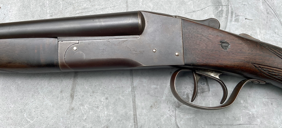 This old scattergun has the same engraved scene on both sides, mostly worn away. That gouge in the stock appeared ancient 40+ years ago when I first saw this gun. (Photo © Russ Chastain)