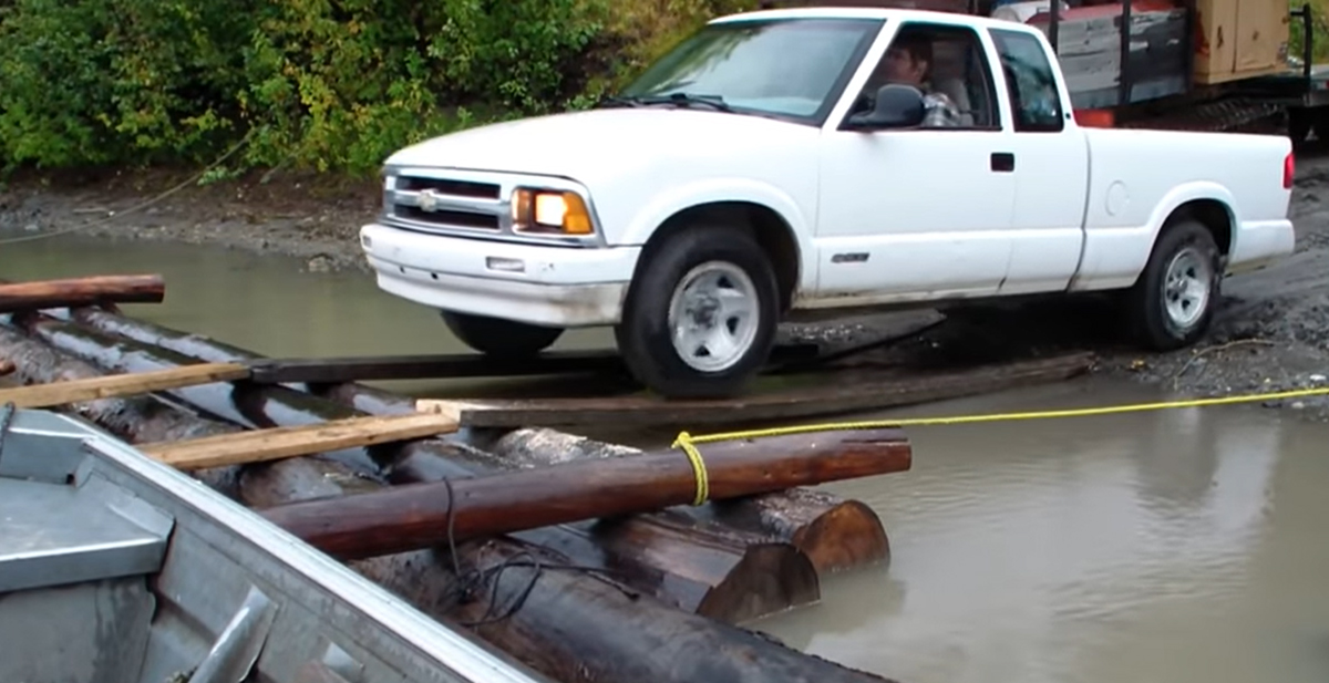 Stan Zuray of Yukon Men Moving a Pickup Truck on a Log Raft