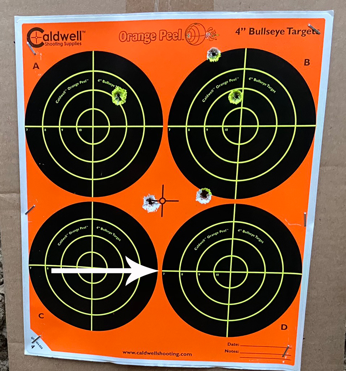 Two 150-yard groups. Top 3 aimed at center of paper, hot barrel. Arrow indicates aim point for bottom cold-barrel group. (Photo © Russ Chastain)