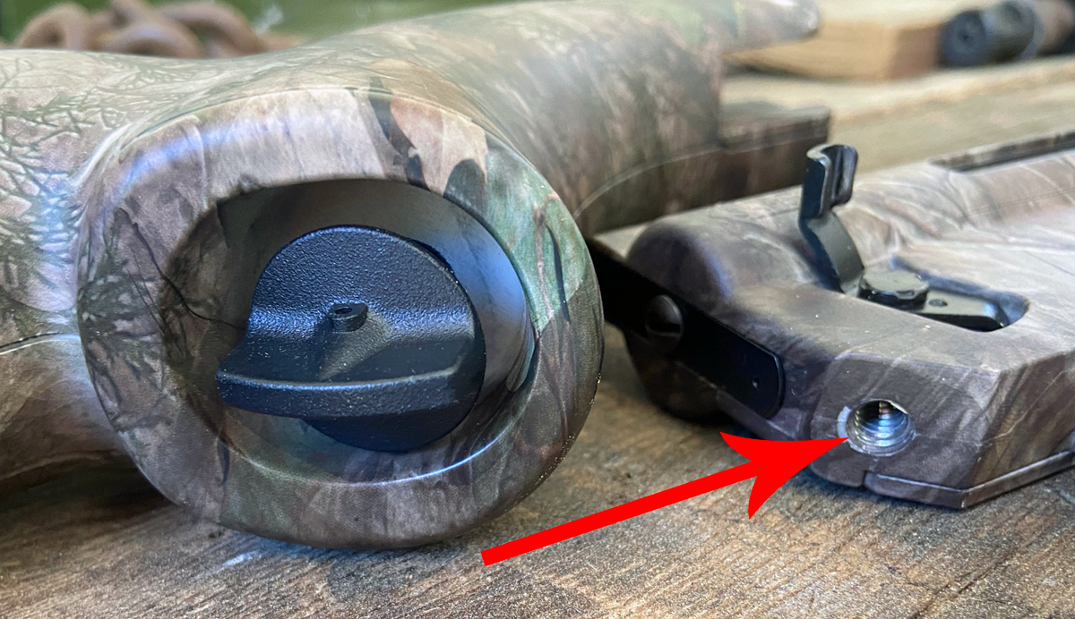 Thumb screw in pistol grip of stock. Arrow indicates threaded hole in receiver. (Photo © Russ Chastain)